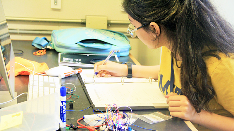 Summer Science program student writing in a notebook