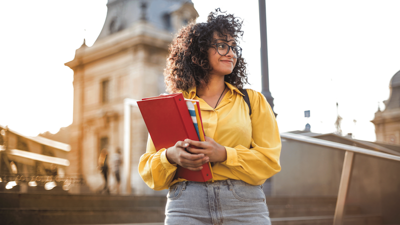 Image of a young woman standing outside holding notebooks