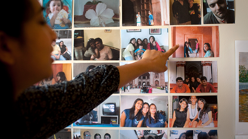 Student pointing to a collage of photos on her wall