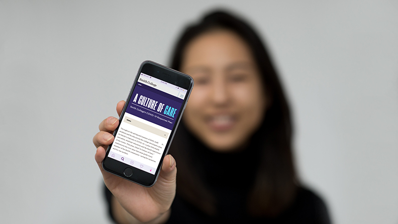 Student holding a mobile phone showing the Smith College COVID-19 website