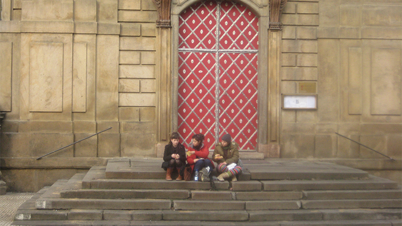 Photo of students sitting on a step in the Czech Republic