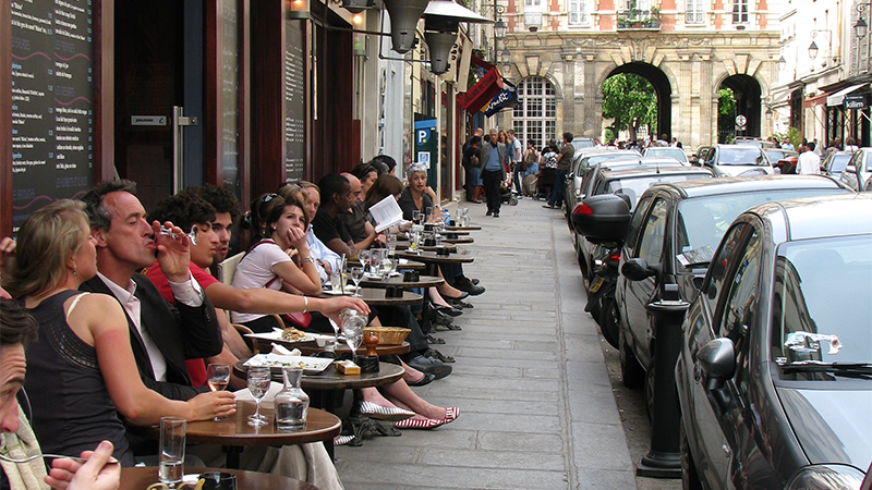 People dining on the street, outside of a Paris cafe