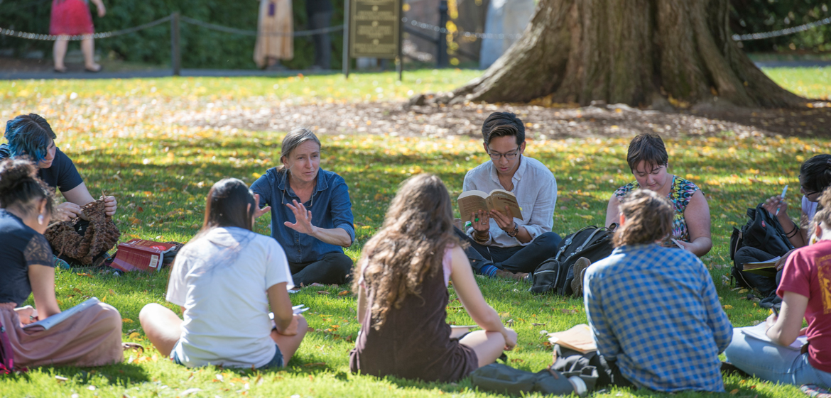Students form a circle on the grass in an outdoor classroom