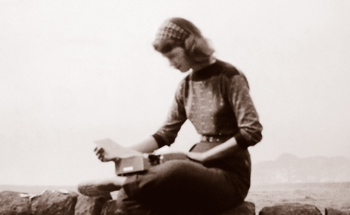 Sylvia Plath sitting on a stone wall, 1957