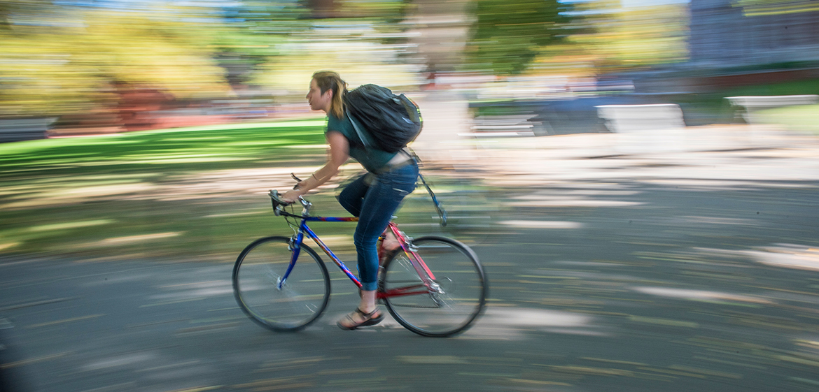 Student riding a bike on campus
