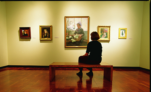 Student sitting on a bench looking at paintings inside the art museum