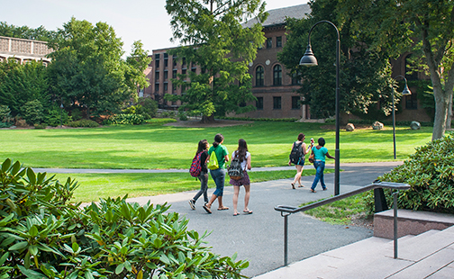 Five students with backpacks walking on campus in late summer