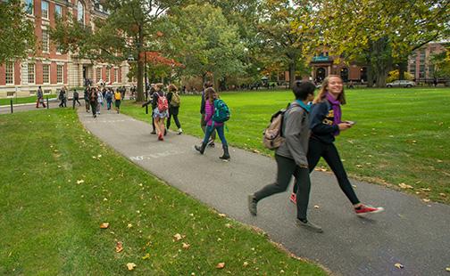Students walking on a sidewalk near Seelye Hall