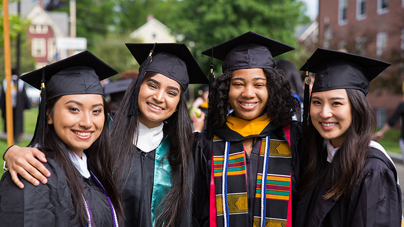 Four students in regalia pose for the camera