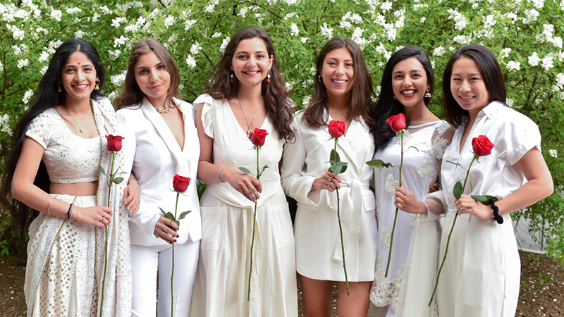 Six students holding red roses on Ivy Day