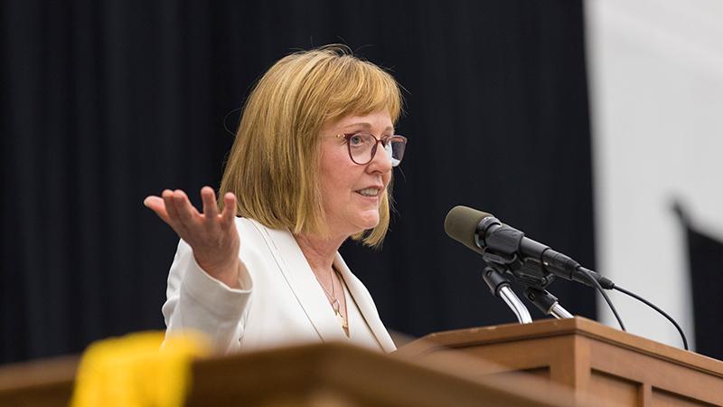 President Kathy McCartney at the podium