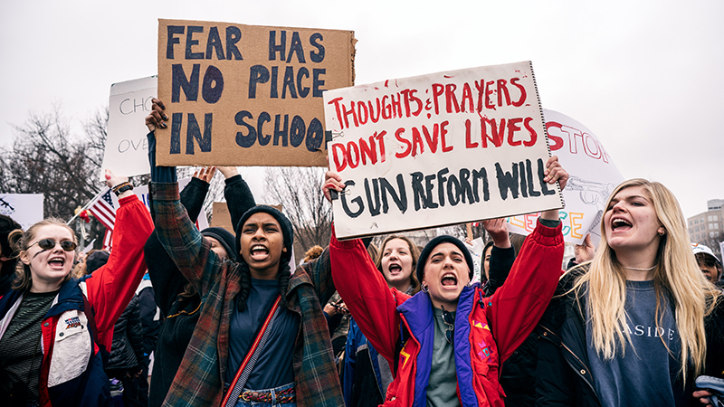 Students holding signs protesting gun violence in schools