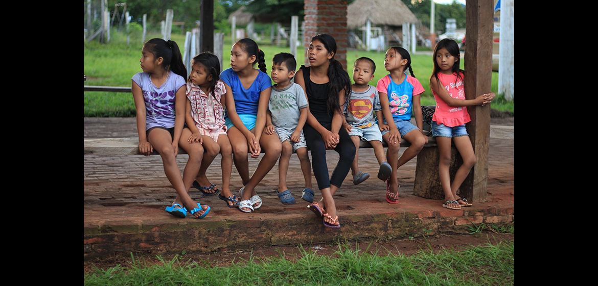 A photo of eight Bolivian children from the Santa Rita community in the Amazon basin sitting on a bench.