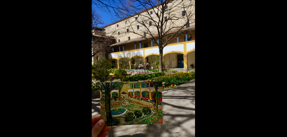 A photo of a hand holding up a postcard showing a painting of the location beyond the postcard.