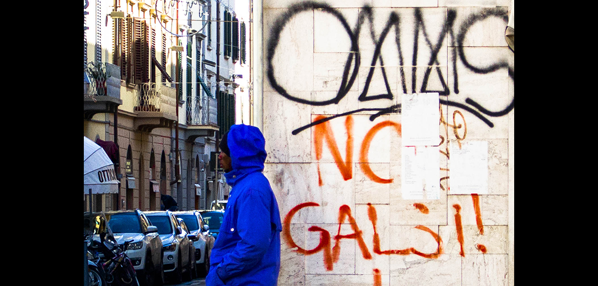 A photo of a man standing on a street corner with graffiti behind him.