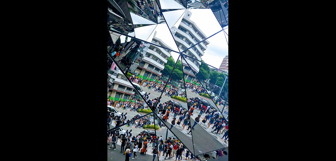 A photo of a mirrored reflection of streets in a popular shopping district in Tokyo.