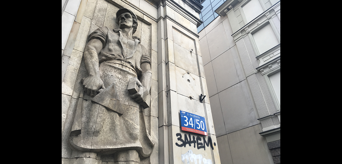 A photo of a communist era relief still standing in the facade of an old building on Marszalkowska street in Warsaw.