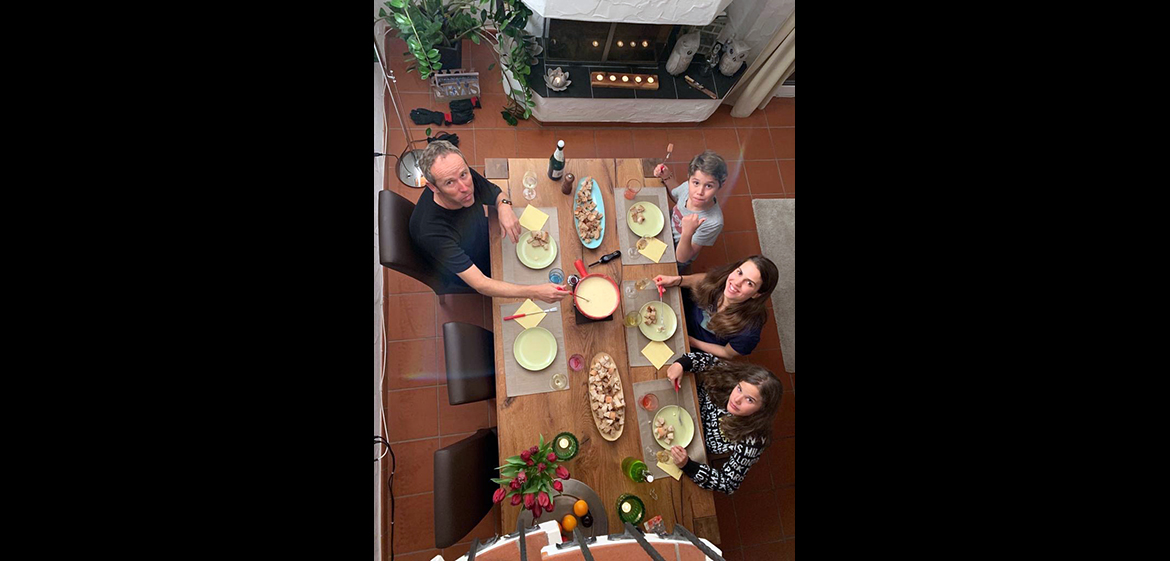 An overhead photo of a family eating fondue.
