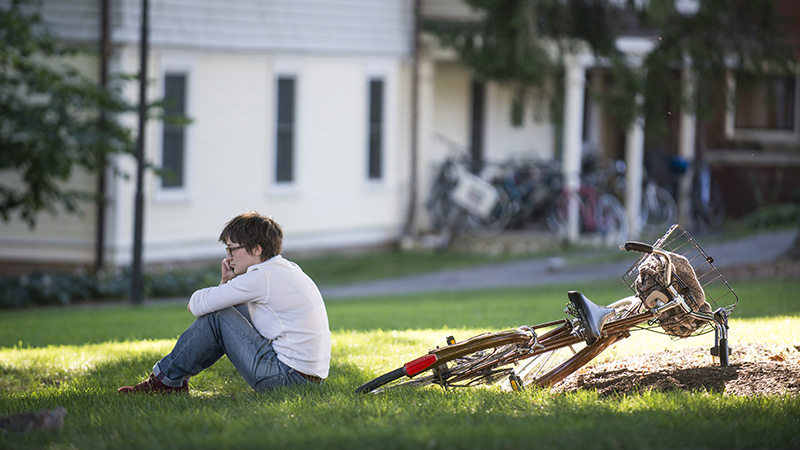 Student sitting on grass, talking on cell phone, with bicycle leaning on grass behind her