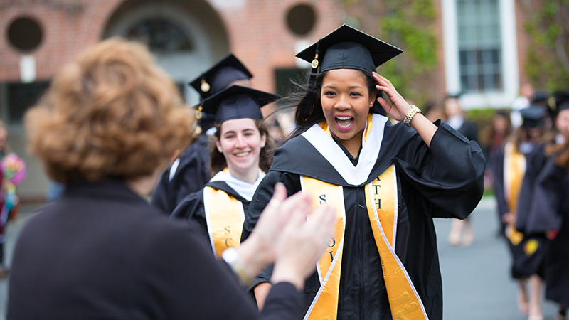 A line of students in caps and gowns marching into Commencement exercises