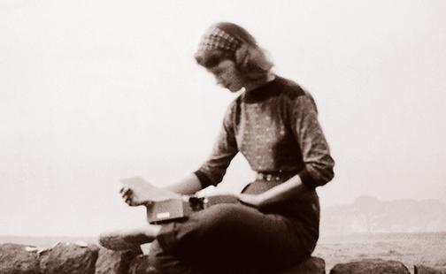 Sylvia Plath sitting on a stone wall, 1957