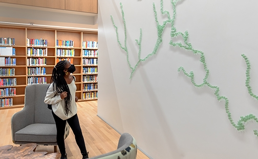 Student looking at Maya Lin sculpture of the Mill River in Neilson Library