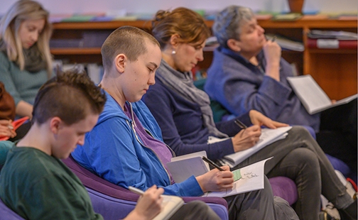 Five students taking notes in a class