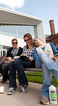 Photo of three students sitting on a bench outside of the Campus Center