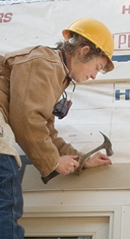 Student in a hardhat working on a Habitat for Humanity project