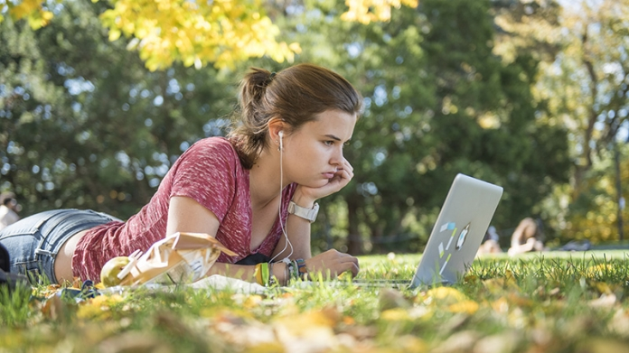Student lying on the grass looking at her laptop screen