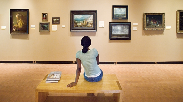 Student on a bench in the museum looking at paintings on the wall