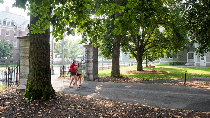 Two students walking through the entry gate to campus