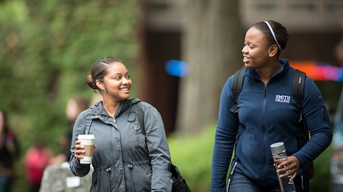 Two students with coffee cups walking on campus