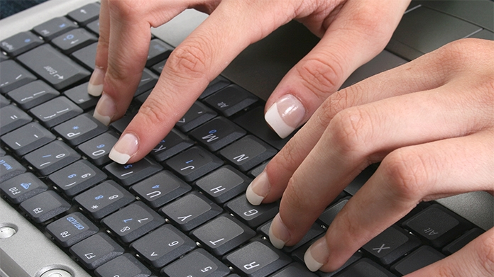Image of a woman's fingernails on a computer keyboard