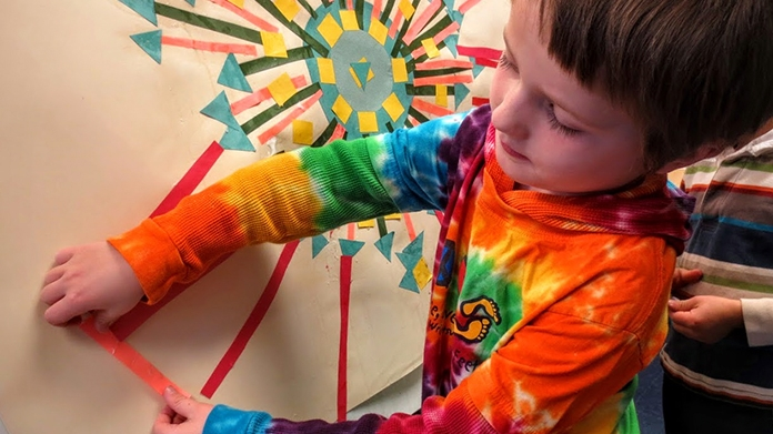 Boy making a collage with colors of paper