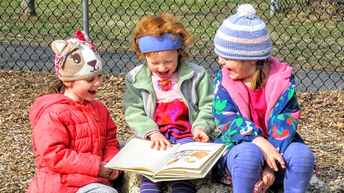 Three girls sharing a book