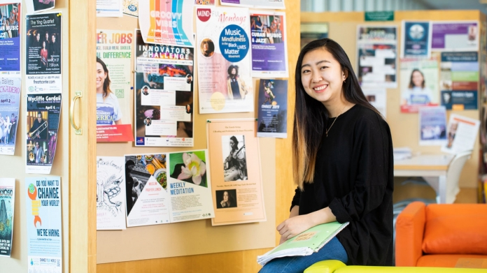 Student in front of a bulletin board covered with posters