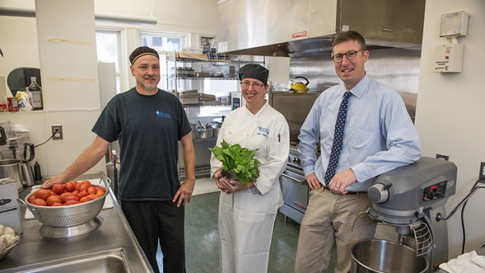 Andy Cox with two dining employees in one of the kitchens