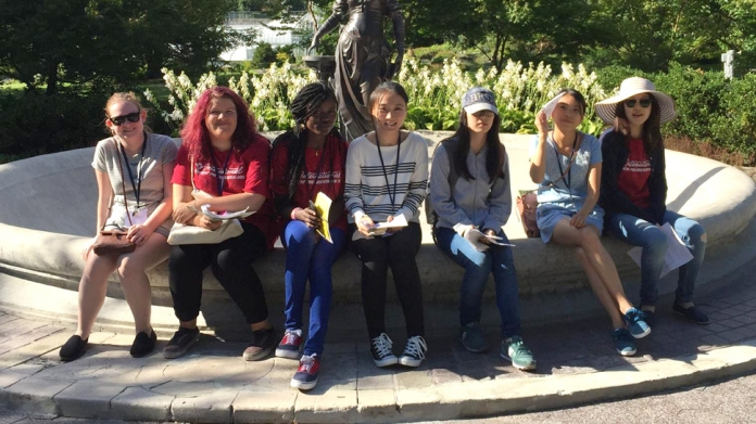 A group of international students sit by fountain, Smith College