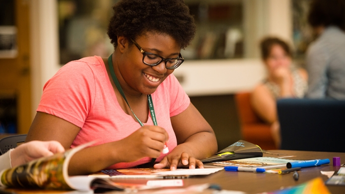 Young woman puts together history journal during Smith College's women's history program