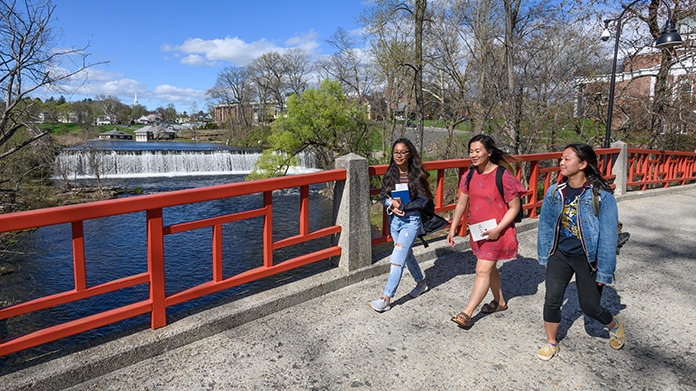 Three students walking across the bridge