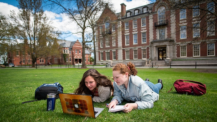 Two students outside looking at a laptop