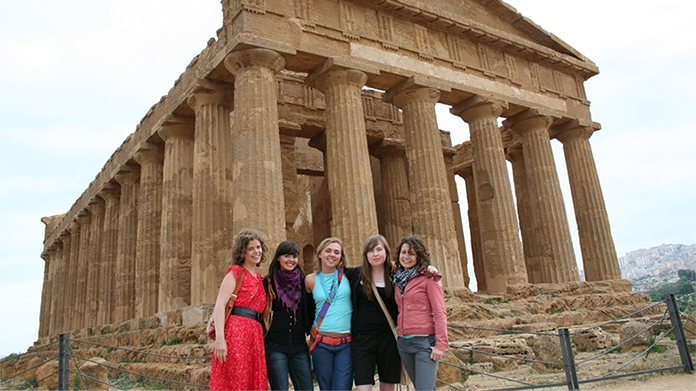 Photo of students posing in front of ancient ruins in Italy