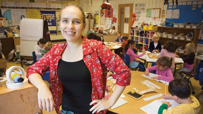Smith student standing in a child's classroom where she volunteers