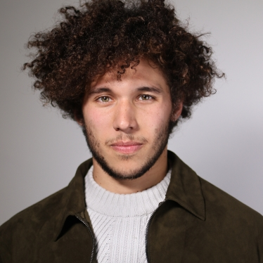 Miguel is a light skinned man with a curly afro, shadow of a mustache and beard in a white turtle neck with brown jacket.