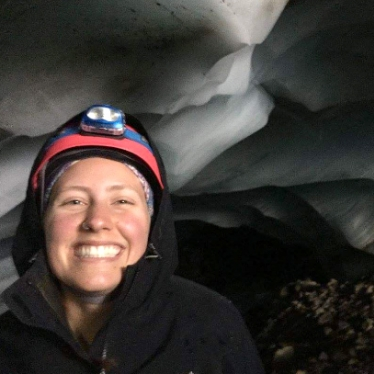 Smith student Molly Peek wears headlamp and stands surrounded by ice