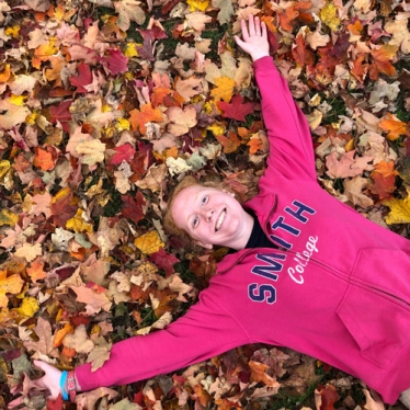 Maddie Wettach laying in autumn leaves.