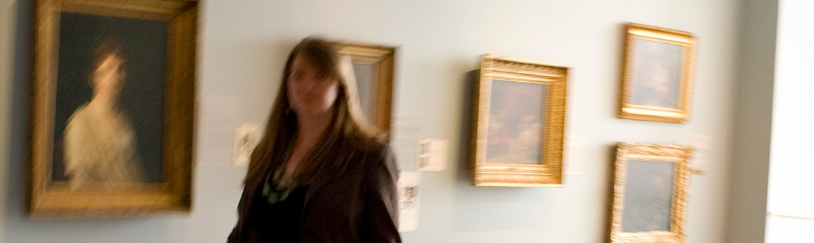 A student walking past artwork in the museum