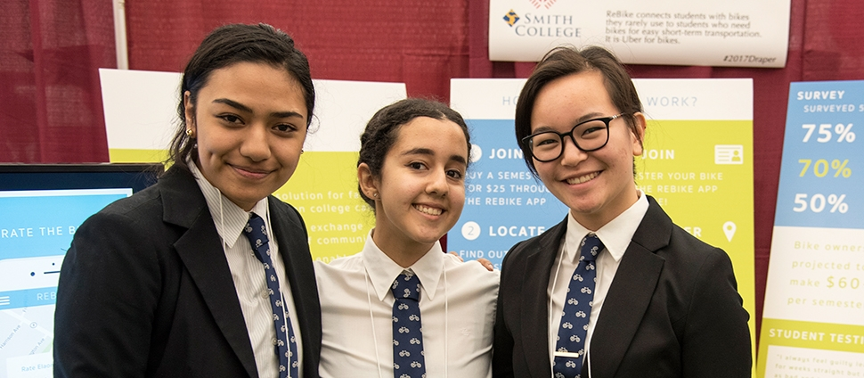 Three students in front of their booth at the Draper Competition