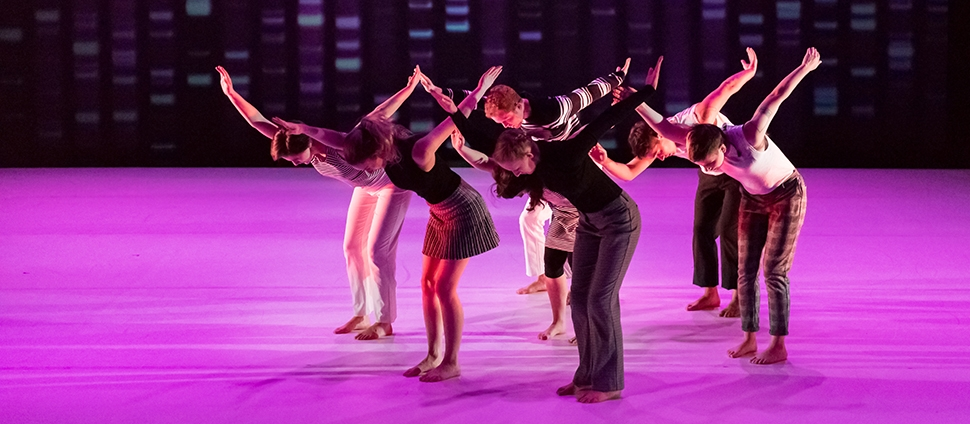 Dance performance with predominantly purple lighting